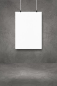 Biały plakat wiszący na ciemnej betonowej ścianie z klipsami. pusty szablon makiety