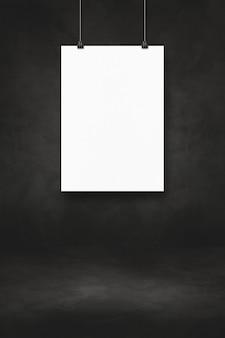 Biały plakat wiszący na czarnej ścianie z klipsami. pusty szablon makiety
