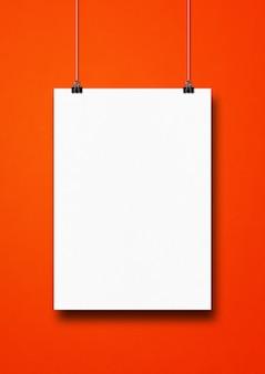Biały plakat wiszący na czerwonej ścianie z klipsami