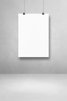 Biały plakat wiszący na jasnej betonowej ścianie z klipsami. pusty szablon makiety