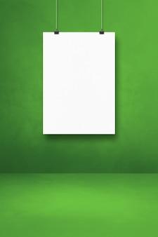 Biały plakat wiszący na zielonej ścianie z klipsami. pusty szablon makiety