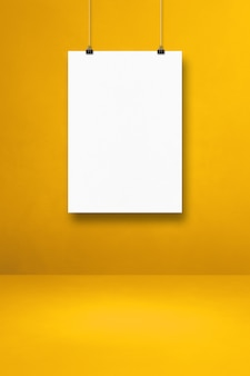 Biały plakat wiszący na żółtej ścianie z klipsami. pusty szablon makiety