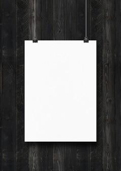 Biały plakat zawieszony na czarnej drewnianej ścianie za pomocą klipsów. pusty szablon makiety