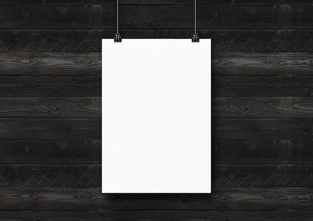 Biały plakat zawieszony na czarnej drewnianej ścianie za pomocą klipsów