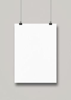 Biały plakat zawieszony na czystej ścianie za pomocą klipsów.