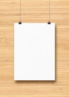 Biały plakat zawieszony na drewnianej ścianie za pomocą klipsów. pusty szablon makiety