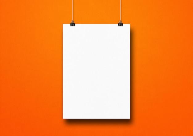 Biały plakat zawieszony na pomarańczowej ścianie za pomocą klipsów. pusty szablon makiety