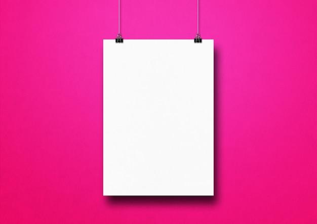 Biały plakat zawieszony na różowej ścianie za pomocą klipsów.