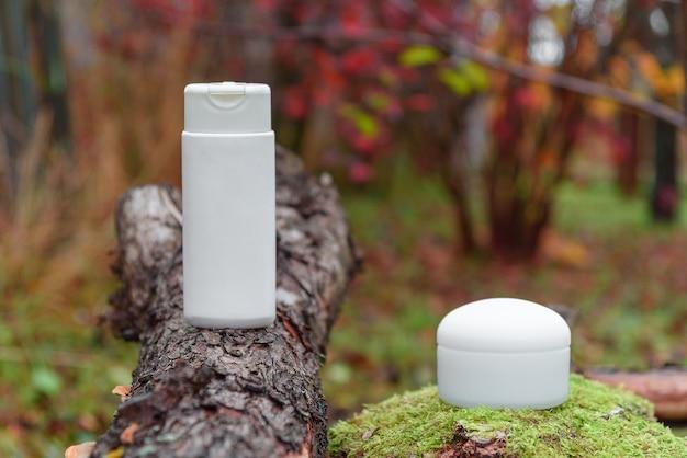 Biały plastikowy pojemnik na trawie i słoik do kremu osmetycznego na korze drzewa
