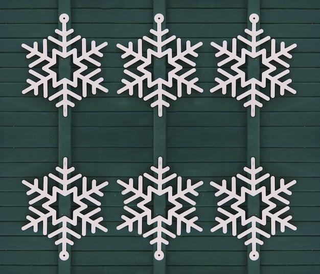 Biały płatek śniegu na zielonych drewnianych drzwiach świątecznych dekoracji