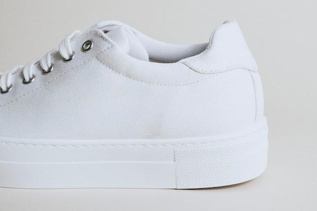 Biały płócienny sneaker kobiety na białym tle