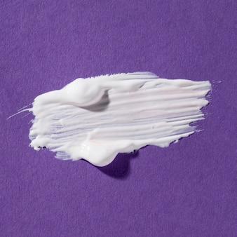 Biały pociągnięcie pędzla na fioletowym tle
