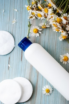 Biały pojemnik na butelkę z ziołowymi kwiatami rumianku.