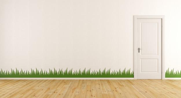 Biały pokój z zamkniętymi drzwiami i naklejoną trawą na ścianie