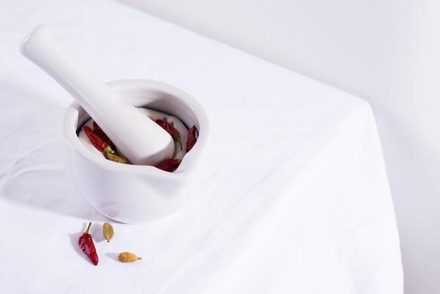 Biały porcelana tłuczek z moździerzem z chili pieprzami i kardamon odizolowywający na tkanina stole, kopii przestrzeń