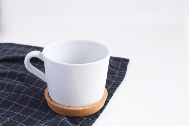Biały porcelanowy kubek i czarna serwetka w kratkę