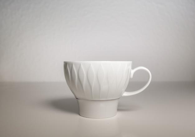 Biały porcelanowy kubek na białym tle