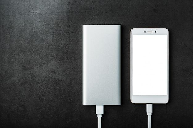 Biały powerbank ładuje smartfon. uniwersalna zewnętrzna bateria do gadżetów wolne miejsce.
