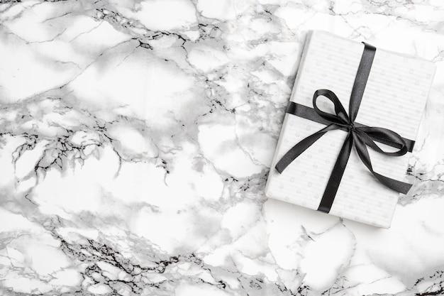 Biały prezent na boże narodzenie z czarną wstążką