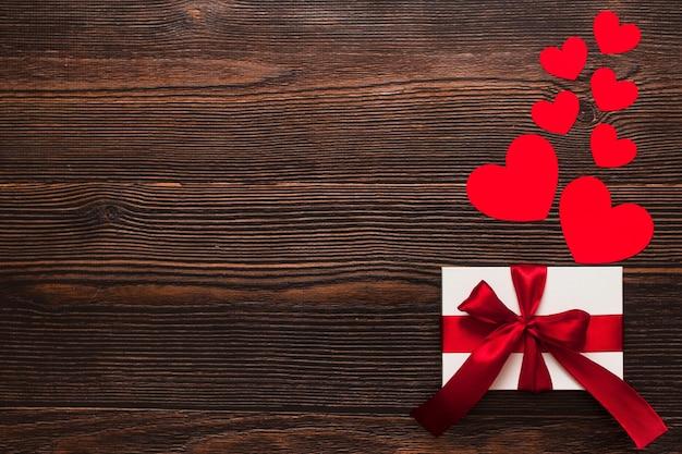 Biały prezent z czerwoną wstążką i serca papieru na białym tle na ciemnym tle drewniane. widok z góry na uroczysty ciepły flatlay. koncepcja walentynki i boże narodzenie. copyspace.