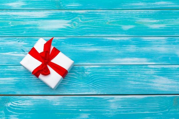 Biały prezenta pudełko z czerwonym faborkiem na błękitnym drewnianym tle, odgórny widok