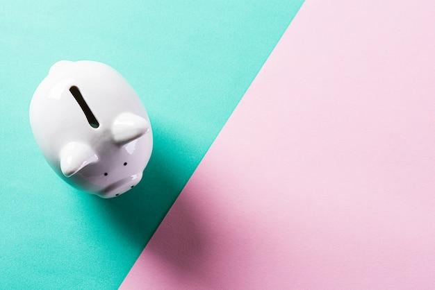 Biały prosiątko bank na pastel ścianie dla oszczędzania pieniądze pojęcia.