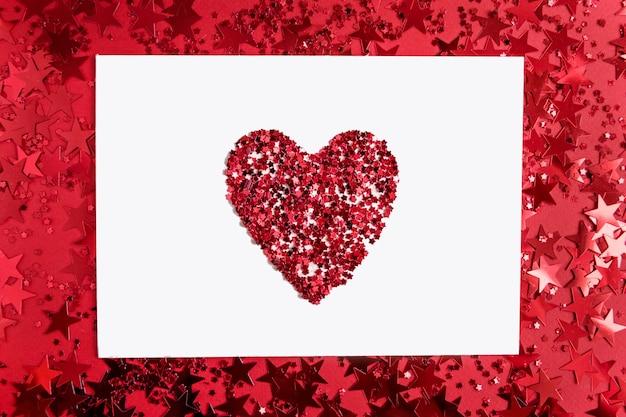 Biały prostokątny papier z serduszkiem pośrodku na czerwono z konfetti w postaci gwiazdek