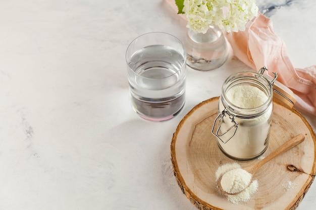 Biały proszek kolagenu w drewnianej łyżce, szklance wody i kwiatku