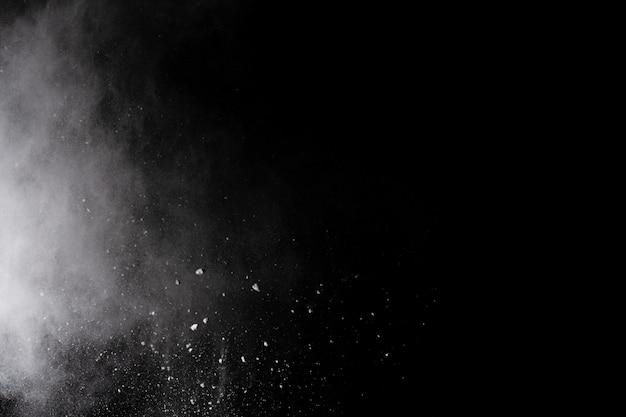 Biały proszek wybuch na czarnym tle.