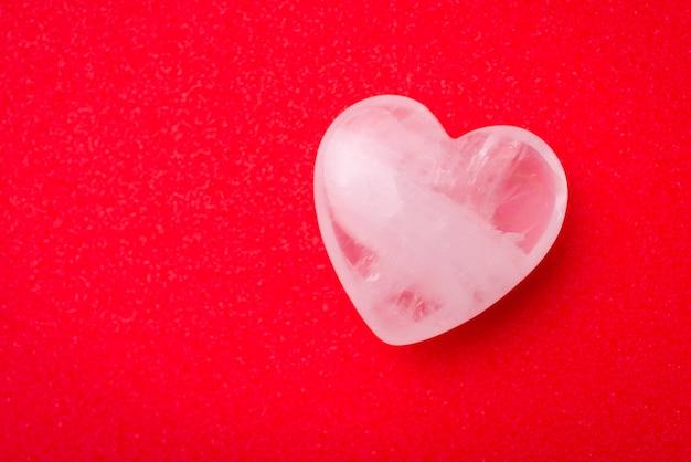 Biały przezroczysty kamień w kształcie serca na czerwonym stole
