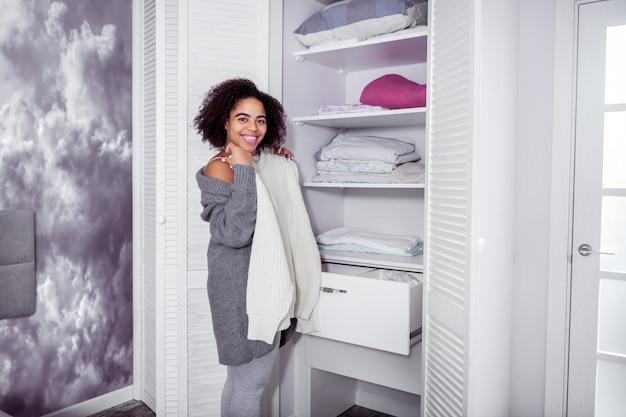 Biały przytulny sweter. uśmiechnięta, wesoła kobieta, stojąca przed szafą, przywiązująca do ciała biały, oversizowy sweter