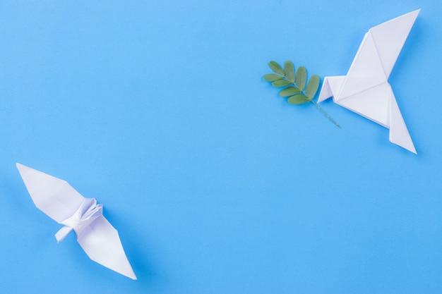 Biały ptak wykonany z papieru niosącego gałąź liścia