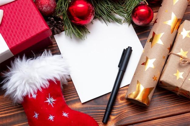 Biały pusty arkusz na list lub listę na drewnianym stole z dekoracjami świątecznymi i noworocznymi