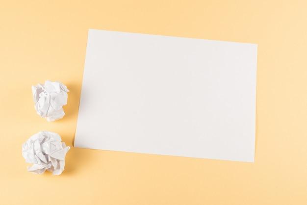 Biały pusty arkusz papieru na beżowym tle.