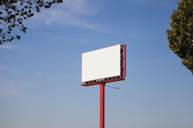 Biały pusty billboard dla reklamy przeciw niebieskiemu niebu z drzewami