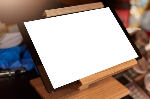 Biały pusty ekran cyfrowego tabletu na drewnianym stojaku na tablet