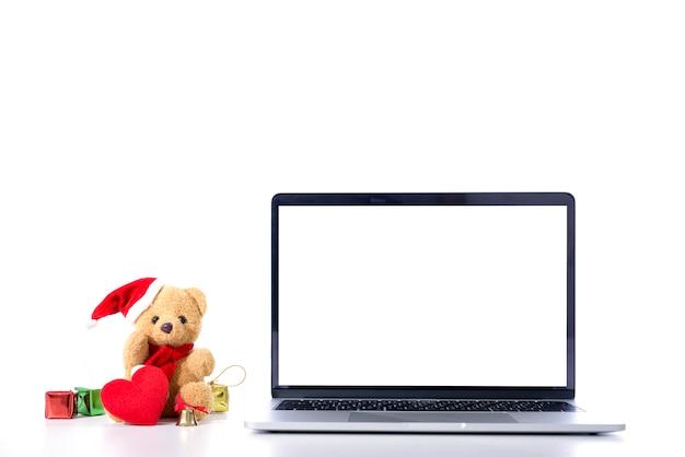 Biały pusty ekran komputer i santa claus niedźwiedź z czerwonym kapiszonem odizolowywającym