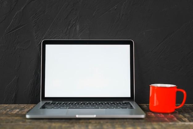 Biały pusty ekran laptopa i czerwony kubek kawy na drewnianym stole