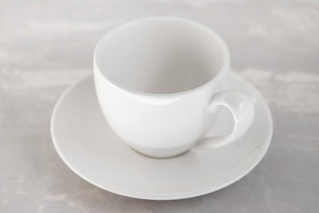 Biały pusty kubek na ceramicznym tle