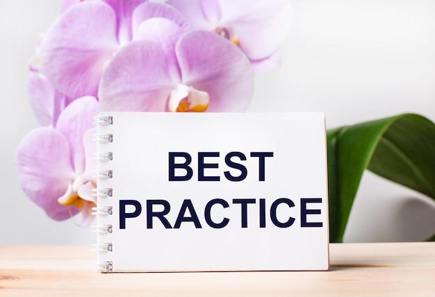 Biały pusty notatnik z napisem najlepsza praktyka na stole na tle jasnoróżowej orchidei.