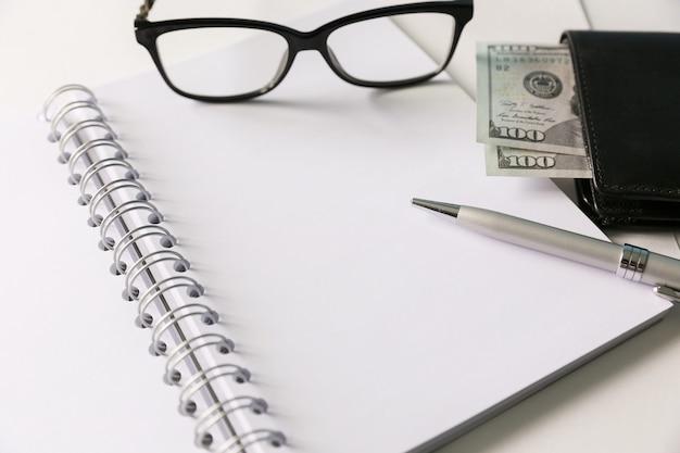 Biały pusty notatnik ze srebrnym piórem i okularami. trochę pieniędzy i portfela znajdują się blisko niego.