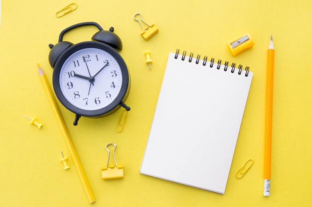 Biały, pusty notatnik, żółte ołówki, artykuły papiernicze i czarny budzik na żółtym, płaskim leżaku