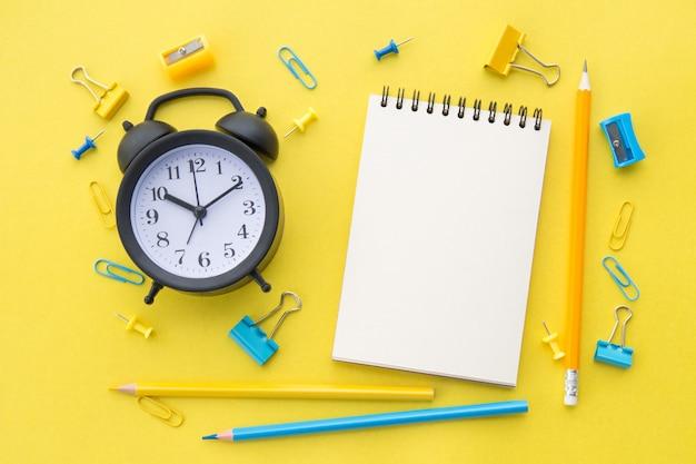 Biały, pusty notatnik, żółto-niebieskie ołówki, artykuły papiernicze i czarny budzik na żółtym, płaskim leżaku
