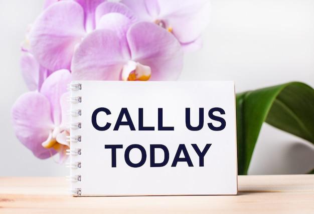 Biały pusty notes z napisem zadzwoń do nas dziś na stole na tle jasnoróżowej orchidei.