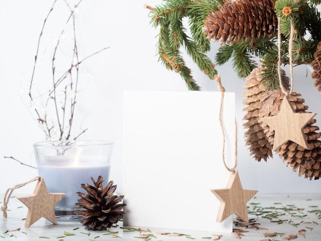 Biały pusty papier na stole z wystrojem świątecznym świeca bukiet jodły i drewniane wieszaki gwiazda na białym tle