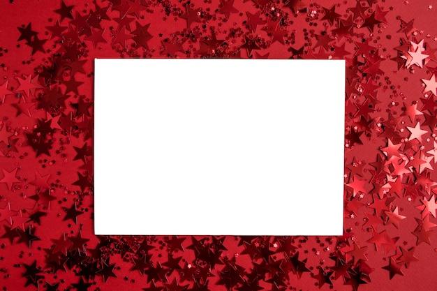 Biały pusty prostokątny papier na czerwono z konfetti w postaci gwiazdek