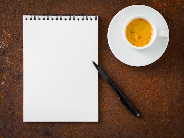 Biały pusty pusty arkusz notesu spirala, ołówek i filiżanka kawy na zardzewiałe