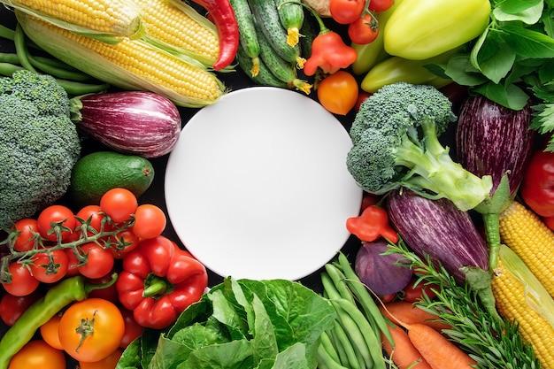 Biały pusty talerz na tle świeżych organicznych warzyw.