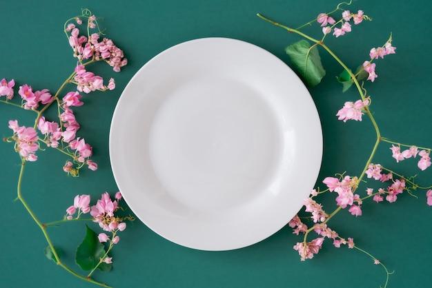 Biały pusty talerz na tle zwykłego zielonego stołu otoczony pięknym różowym kwiatowym i świeżym zielonym płatkiem płasko leżał, widok z góry na pustym porcelanowym naczyniu otoczonym różowymi kwiatami i bezpłatnej kopii przestrzeni.