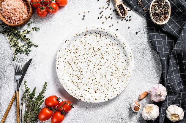Biały pusty talerz pośrodku pomidorów i przypraw